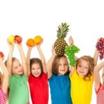 Smiling children holding fruit over their heads
