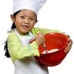 Young child dressed as a chef with mixing bowl