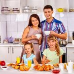 A family stands together in a kitchen.
